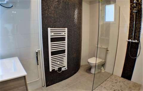 salle de bains / douche carrelée avec toilette et fenêtre