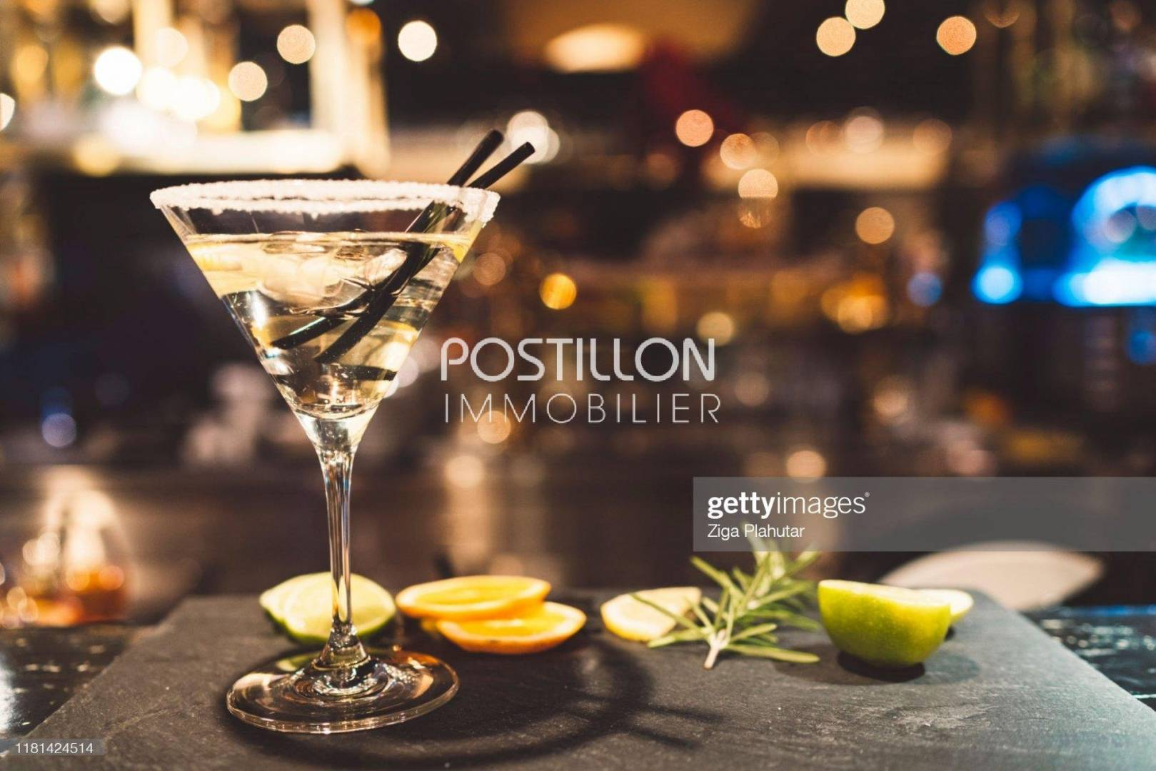 Glass of martini on a grnished surface with lemon slices and rosemary. Black bakground. Glas garnished with sugar on the edge.