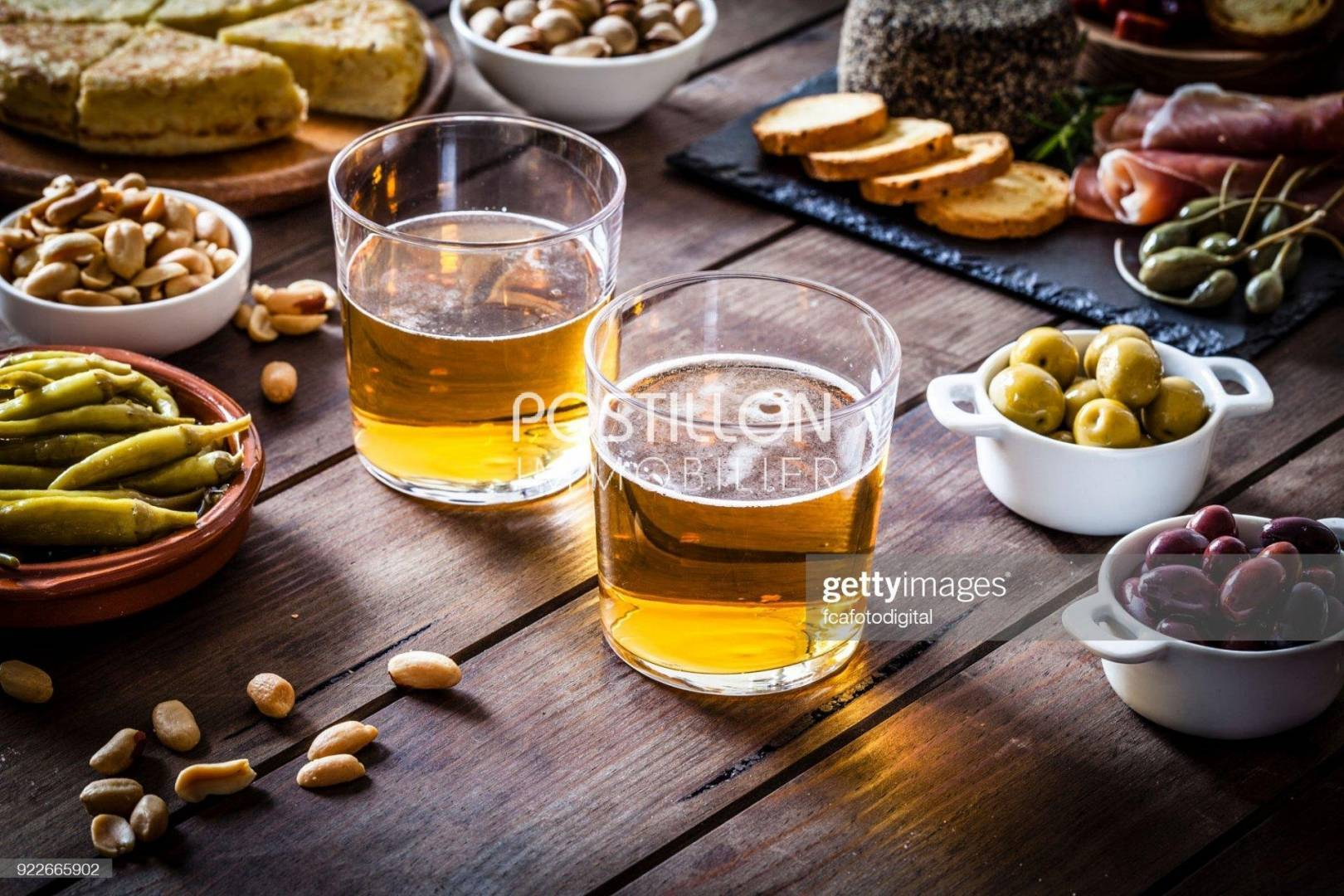 Two beer glasses shot on rustic wooden table with some tapas and appetizer. The beer glasses are at the center of an horizontal frame while some tapas are around them. The composition includes spanish